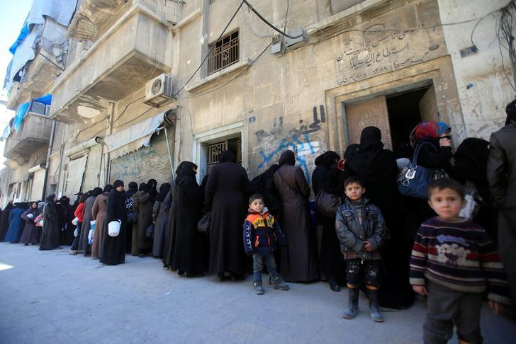 Women and children queue to receive free meals in Aleppo, Syria February 2, 2017. REUTERS/Ali Hashisho