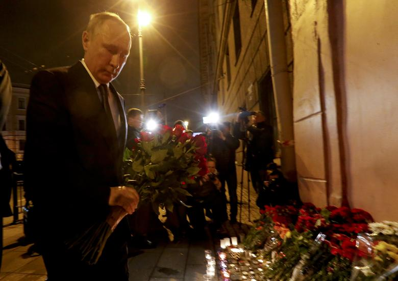 Russian president Vladimir Putin puts flowers down outside Tekhnologicheskiy Institut metro station in St. Petersburg, Russia, April 3, 2017.   REUTERS/Grigory Duko