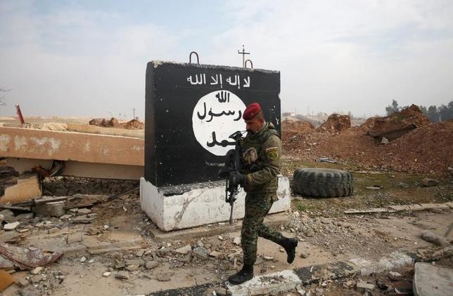 4月4日、過激派組織「イスラム国」(IS)のアブ・アルハサン・アル・ムハジル報道官は、音声メッセージを発表し、米国は「愚か者に支配されている」と述べた。ISがトランプ米大統領について公式に言及したのは、今回が初めて。写真はイスラム国過激派が使う旗を描いた壁。モスル北部で1月撮影(2017年 ロイター/Khalid al Mousily)