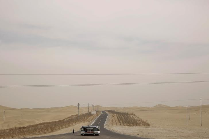 Police keep watch on a road running through the Taklamakan Desert outside Hotan, Xinjiang Uighur Autonomous Region, China, March 21, 2017.  REUTERS/Thomas Peter/Files