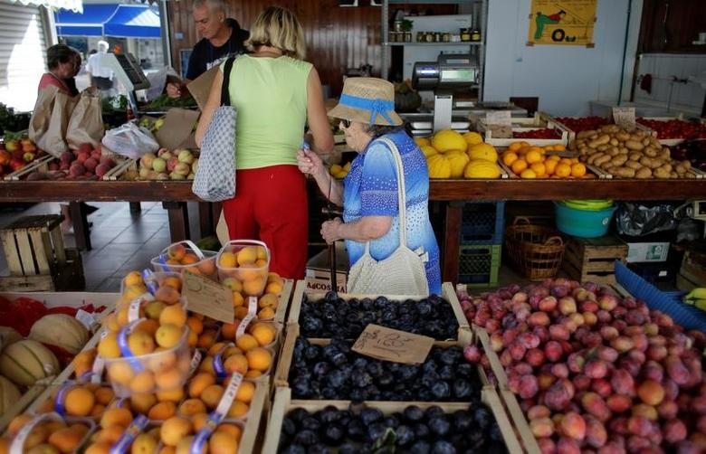 A woman buys fruit and vegetables in a street market in Rome, Italy, August 11, 2016. REUTERS/Max Rossi