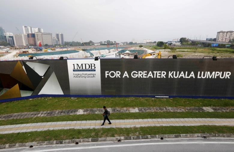 FILE PHOTO - A man walks past a 1 Malaysia Development Berhad (1MDB) billboard at the funds flagship Tun Razak Exchange development in Kuala Lumpur, in this March 1, 2015 file photo.    REUTERS/Olivia Harris/File Photo