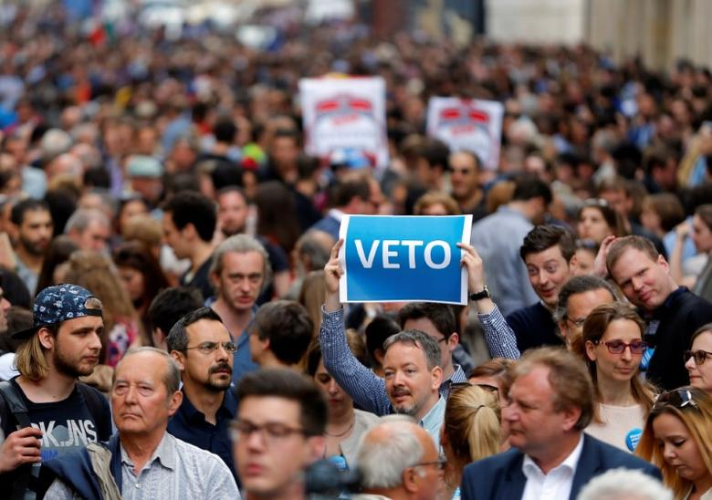 A demonstrator holds up a banner saying ''Veto'' during a rally against a new law passed by Hungarian parliament which could force the Soros-founded Central European University out of Hungary, in Budapest, Hungary, April 4, 2017. REUTERS/Laszlo Balogh
