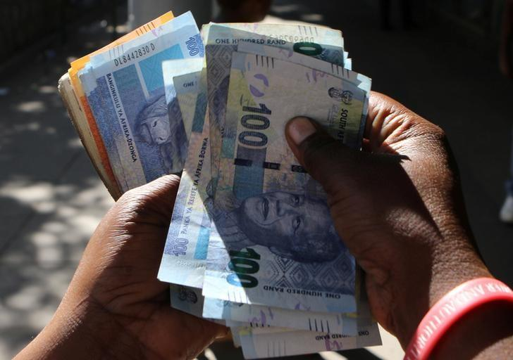 FILE PHOTO: A street money changer counts South African Rands in Harare, Zimbabwe, May 5, 2016.  REUTERS/Philimon Bulawayo/File Photo