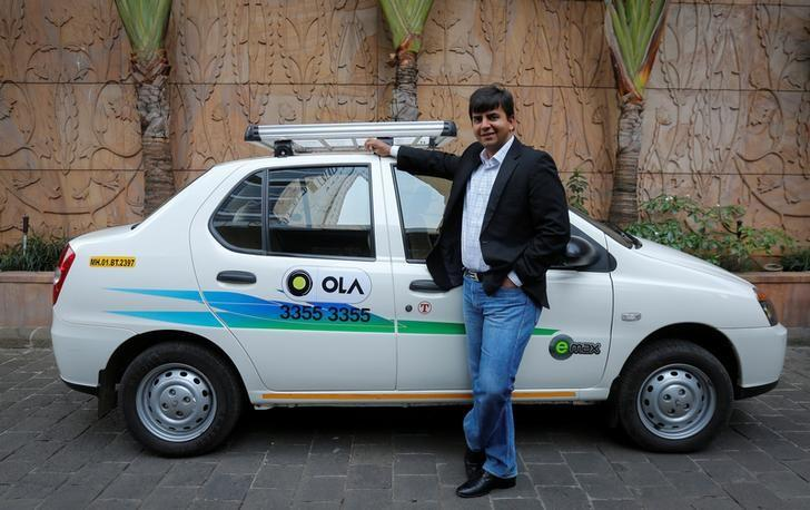 Bhavish Aggarwal, CEO and co-founder of Ola, an app-based cab service provider, poses in front of an Ola cab in Mumbai March 3, 2015. REUTERS/Shailesh Andrade/File Photo - RTSLY9Y