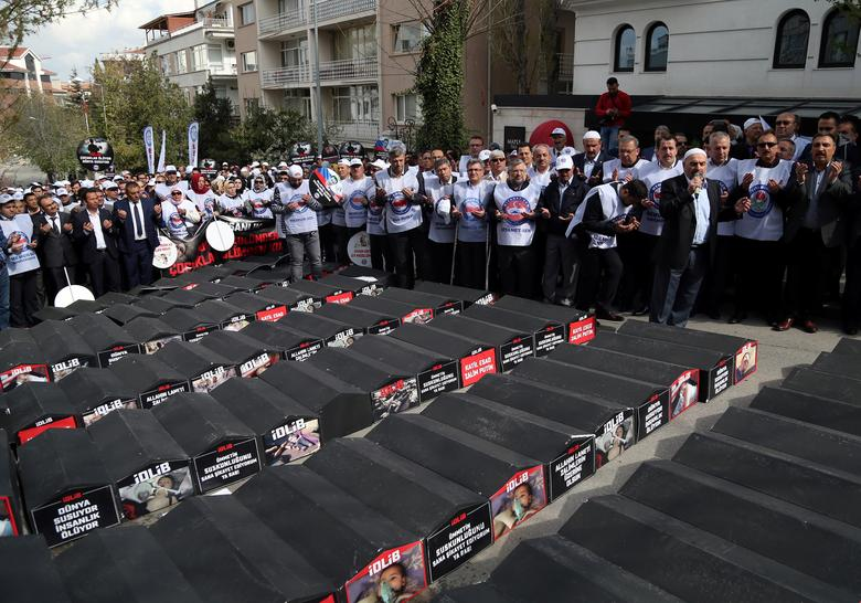 Demonstrators pray next to mock coffins during a protest against Russian and Iran in Ankara, Turkey, April 7, 2017. REUTERS/Stringer