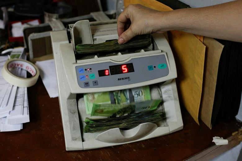 A woman uses a machine to count Venezuelan bolivar notes at an office in Caracas, Venezuela March 21, 2017. REUTERS/Marco Bello