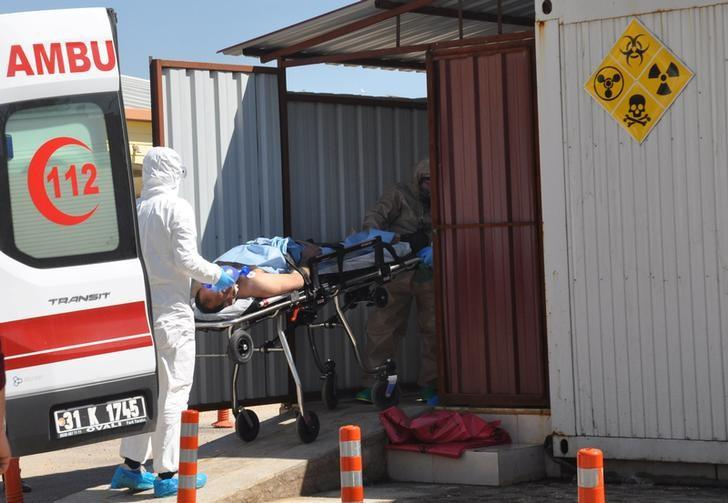 A Syrian man from Idlib is carried by Turkish medics wearing chemical protective suits to a hospital in the border town of Reyhanli in Hatay province, Turkey, April 4, 2017. Ferhat Dervisoglu/Dogan News Agency via REUTERS