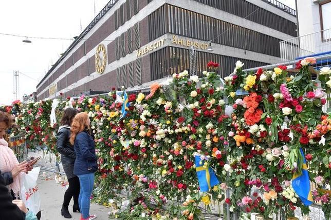 4月8日、スウェーデンの首都ストックホルムでトラックが人混みに突っ込み4人が死亡、15人が負傷した事件で、現地の警察は、身柄を拘束したウズベキスタン出身の男がトラックを運転していた実行犯の可能性が高いとの見方を示した。写真は、現場で花を手向ける人々。提供写真(2017年 ロイター/TT News Agency/Jonas Ekstromer via REUTERS)