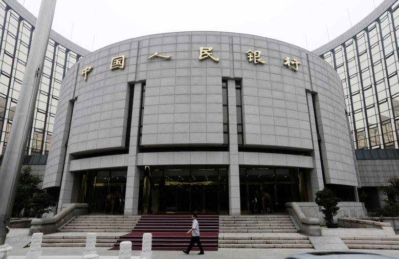 FILE PHOTO: A staff member walks in front of the headquarters of the People's Bank of China (PBOC), the central bank, in Beijing, June 25, 2013.  REUTERS/Jason Lee/File Photo