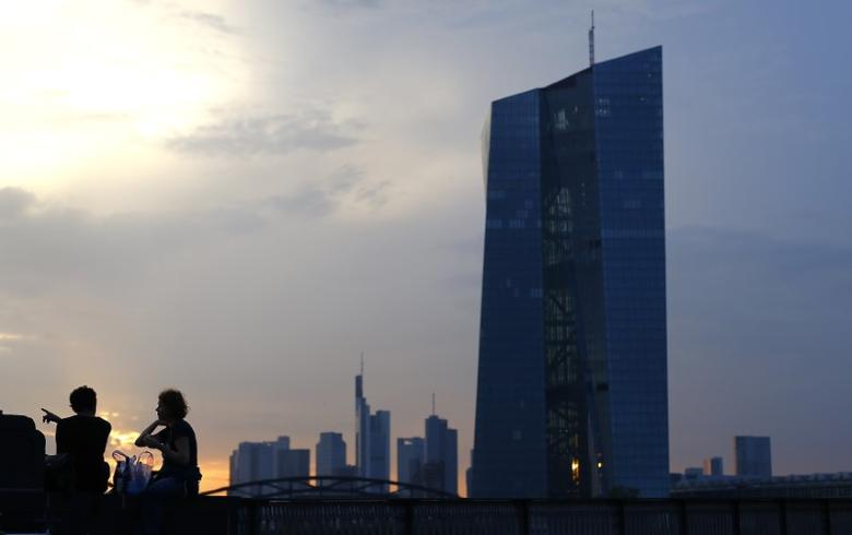 People gesture as they sit in front of the skyline of the banking district (C) and the new headquarters of the European Central Bank (R) in Frankfurt, September 18, 2014.  REUTERS/Kai Pfaffenbach
