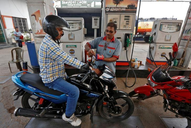 A worker uses a card machine to receive payment from a motorcyclist at a fuel station in Kolkata, India, February 1, 2017. REUTERS/Rupak De Chowdhuri/File Photo
