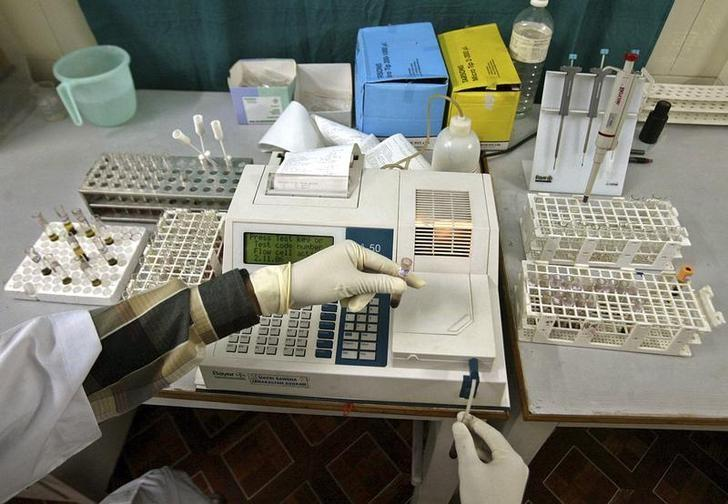 A laboratory assistant examines blood samples inside a laboratory in Siliguri November 2, 2006. REUTERS/Rupak De Chowdhuri/File Photo