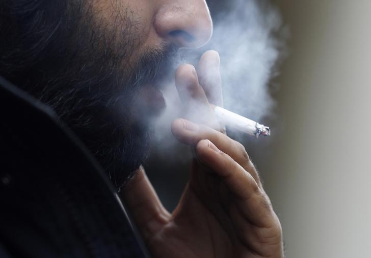 A man smokes a cigarette in central London, Britain February 1, 2010.    REUTERS/Suzanne Plunkett/File Photo