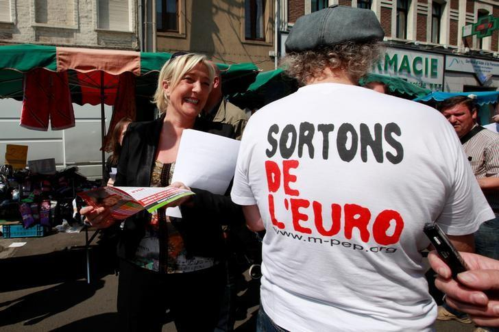 France's far right National Front political party leader Marine Le Pen (L), campaigns at an open-air market in Henin-Beaumont May 29, 2012. T-shirt reads, ''Leave the Euro''.    REUTERS/Pascal Rossignol/File Photo