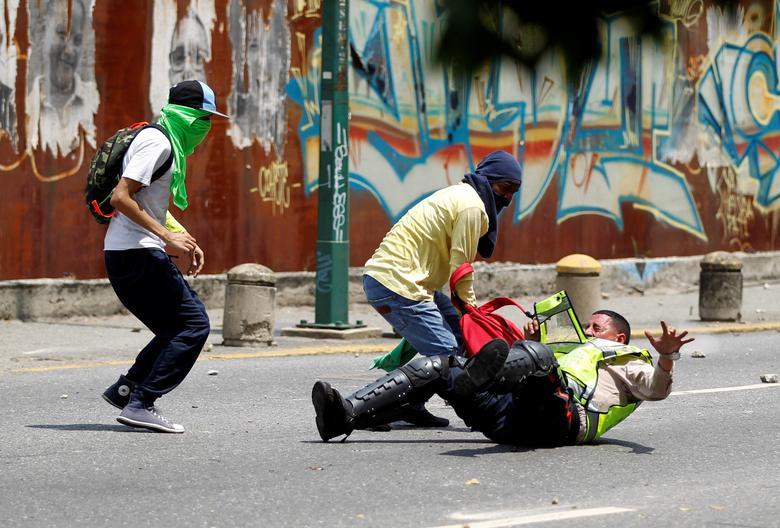 Demonstrators grab a riot police officer at a rally against Venezuela's President Nicolas Maduro's government in Caracas, Venezuela. REUTERS/Christian Veron