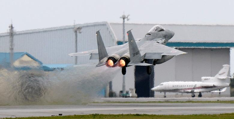 FILE PHOTO: A Japanese Air Self Defense Force F-15 fighter scrambles at the Air Self Defense Force Naha base in Naha, Okinawa prefecture, Japan, in this photo taken by Kyodo April 13, 2015. Kyodo/via REUTERS