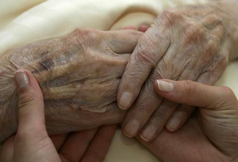 A young carer holds the hands of an elderly woman in a residential home for the elderly in Planegg near Munich in this June 19, 2007 file photo.Michaela Rehle/Files