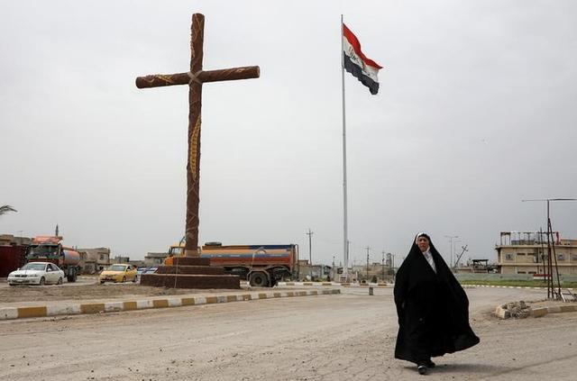 A woman walks past a big cross at the entrance of the town of Qaraqosh, south of Mosul, Iraq, April 13, 2017. REUTERS/Marko Djurica
