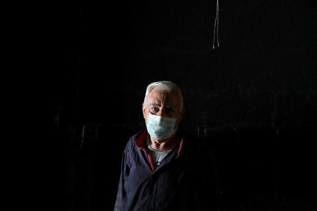 Sabri, a restaurant owner, poses for a picture as he cleans his burnt-out restaurant in the town of Qaraqosh, south of Mosul, Iraq, April 13, 2017. REUTERS/Marko Djurica