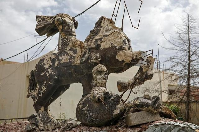 A damaged statue is seen outside a church in the town of Qaraqosh, south of Mosul, Iraq, April 12, 2017. REUTERS/Marko Djurica