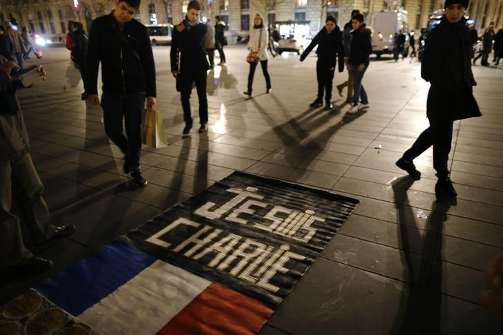 People gather on the Place de la Republique square to pay tribute to the victims of last year's shooting at the French satirical newspaper Charlie Hebdo, in Paris, France, January 7, 2016. REUTERS/Stephane Mahe/Files