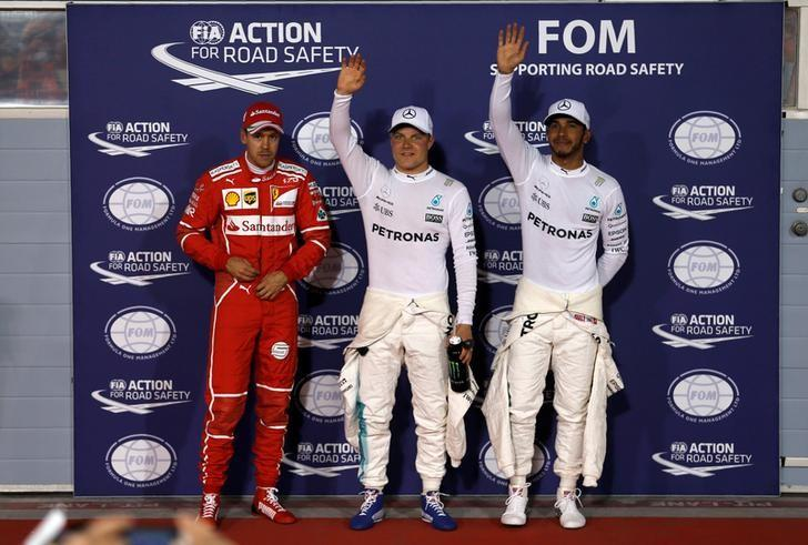 Formula One - F1 - Bahrain Grand Prix - Sakhir, Bahrain - 15/04/17 - Ferrari Formula One driver Sebastian Vettel of Germany, Mercedes Formula One driver Valtteri Bottas of Finland and Mercedes Formula One driver Lewis Hamilton of Britain celebrate after the qualifying session. REUTERS/Hamad I Mohammed