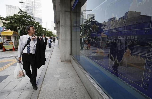 4月17日、東京株式市場で日経平均は5日ぶりの小反発となった。1ドル108円台前半まで円高方向に振れた為替が重しとなり、取引時間中の年初来安値を連日で更新。写真は株価ボードを見ながら歩く男性。都内で2014年5月撮影(2017年 ロイター/Yuya Shino)