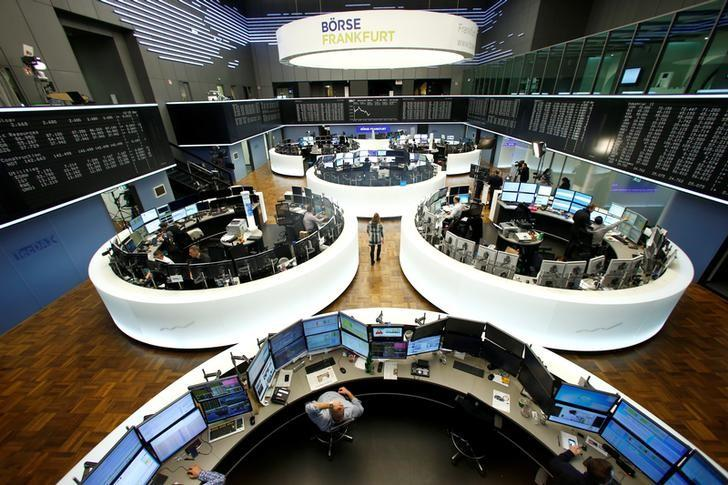 Traders work at their desks in front of the German share price index, DAX board, at the stock exchange in Frankfurt, Germany, February 15, 2017. REUTERS/Ralph Orlowski/Files