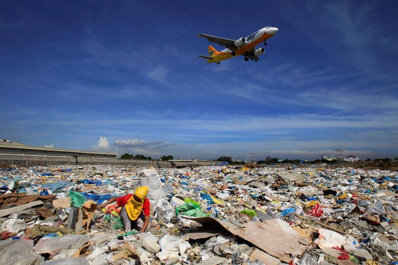 FILE PHOTO: An aircraft flies overhead as a person rummages for recyclables at a garbage dumpsite in Paranaque city, metro Manila June 8, 2014.   REUTERS/Romeo Ranoco/File Photo