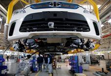 Des employés travaillent sur une voiture électrique dans une usine à Pékin. Le salon de l'automobile de Shanghai sera dominé cette année par une vaste offensive des groupes étrangers dans l'électrique et l'hybride malgré les flottements actuels dans l'arsenal réglementaire chinois pour réduire les émissions. /Photo d'archives/REUTERS/Kim Kyung-Hoon