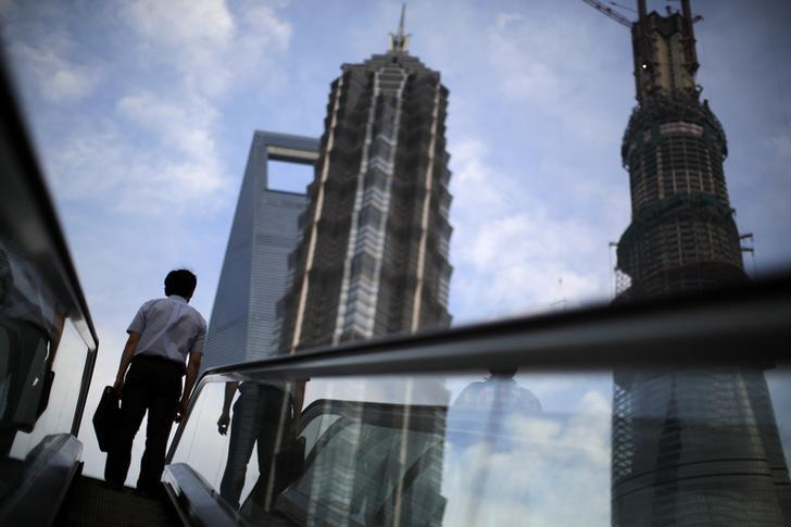 A man rides an escalator near Shanghai Tower (R, under construction), Jin Mao Tower (C) and the Shanghai World Financial Center (L) at the Pudong financial district in Shanghai July 4, 2013. REUTERS/Carlos Barria/Files