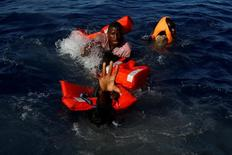 Migrants try to stay afloat after falling off their rubber dinghy during a rescue operation by the Malta-based NGO Migrant Offshore Aid Station (MOAS) ship in the central Mediterranean in international waters some 15 nautical miles off the coast of Zawiya in Libya, April 14, 2017. All 134 sub-Saharan migrants survived and were rescued by MOAS.  REUTERS/Darrin Zammit Lupi