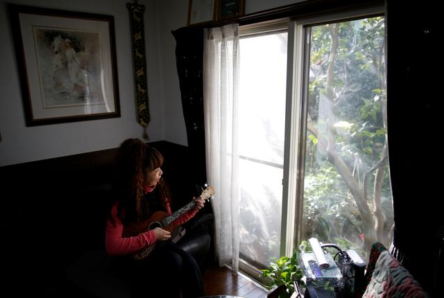 54-y-o Hiromi Tanaka holds a ukulele during an interview with Reuters at her house where she lives with her widowed mother in Tokyo, Japan March 1, 2017.     REUTERS/Issei Kato