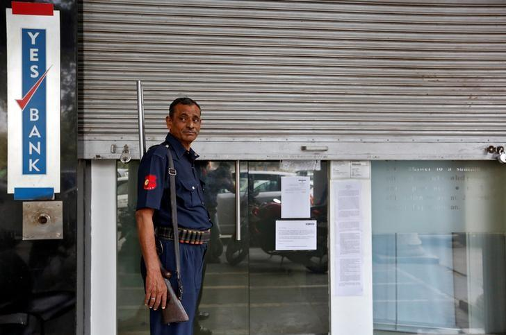 A security guard stands outside a closed Yes Bank branch in New Delhi, India, November 9, 2016. REUTERS/Cathal McNaughton