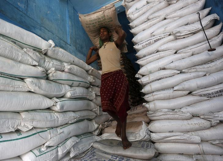A labourer carries a sack filled with sugar in a store at a wholesale market in Kolkata, India, February 15, 2016.  REUTERS/Rupak De Chowdhuri/File Photo