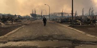 FILE PHOTO --  A Mountie surveys the damage on a street in Fort McMurray, Alberta, Canada in this May 4, 2016 image posted on social media. Courtesy Alberta RCMP/Handout via REUTERS