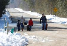 A family that says they are from Colombia walks down Roxham Road toward the U.S.-Canada border leading into Hemmingford, Quebec, Canada March 26, 2017. REUTERS/Christinne Muschi