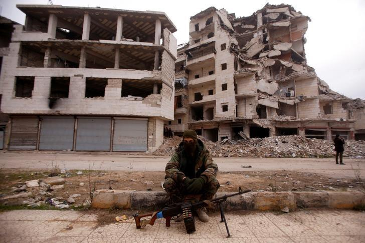 A member of forces loyal to Syria's President Bashar al-Assad sits near damaged buildings in Aleppo's Salaheddine district, Syria December 16, 2016. REUTERS/Omar Sanadiki