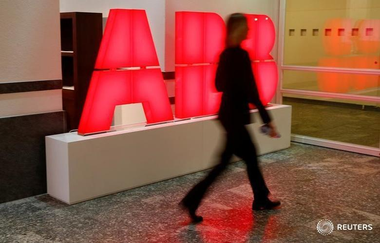 A woman walks past the logo of Swiss power technology and automation group ABB ahead of a news conference to present the company's full-year results in Zurich, Switzerland February 8, 2017. REUTERS/Arnd Wiegmann - RTX30430
