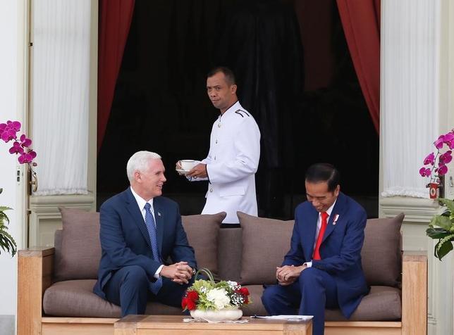 4月20日、アジアを歴訪中のペンス米副大統領(写真左)は、米政権はインドネシアとのより公正な貿易を望んでいると語った。写真右はジョコ・ウィドド・インドネシア大統領(2017年 ロイター/Darren Whiteside)
