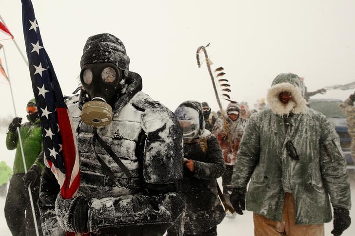 A man takes part in a march with veterans to Backwater Bridge just outside of the Oceti Sakowin camp during a snow fall as ''water protectors'' continue to demonstrate against plans to pass the Dakota Access pipeline adjacent to the Standing Rock Indian Reservation, near Cannon Ball, North Dakota, U.S., December 5, 2016.  REUTERS/Lucas Jackson