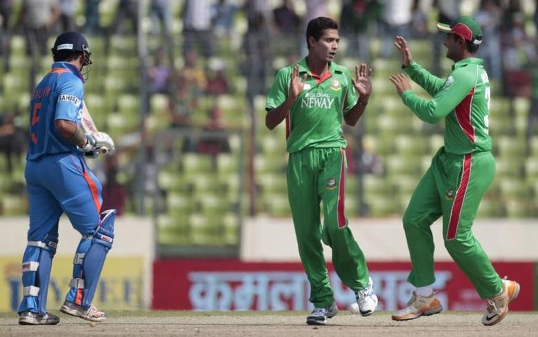 Bangladesh's Tamim Iqbal (R) congratulates bowler Shafiul Islam (C) as he dismissed India's Gautam Gambhir (L) successfully during their One Day International (ODI) cricket match of Asia Cup in Dhaka March 16, 2012. REUTERS/Andrew Biraj/File Photo