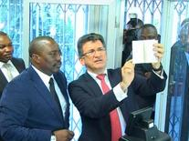 President Joseph Kabila of the Democratic Republic of Congo (L) is seen alongside Semlex CEO Albert Karaziwan during an event to launch the country's new biometric passports at the foreign ministry in Kinshasa in this still image taken from footage shot in November 2015 and made available to Reuters March 19, 2017.  RTNC/Handout via REUTERS TV