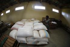 Subsistence farmer Salome Banda stands beside bags of her maize stacked in a warehouse north of Lilongwe, Malawi February 2, 2016.   REUTERS/Mike Hutchings
