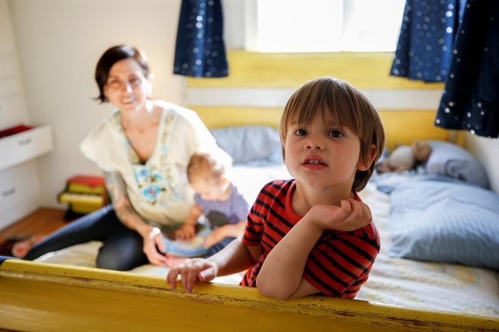 Three and a half year old Wyatt Gries (R) poses on his bed inside his bedroom while his mother Amanda Gries holds his 12 month old brother Eli Gries in the Del Rey neighborhood of Los Angeles, California, United States April 4, 2017. REUTERS/Danny Moloshok