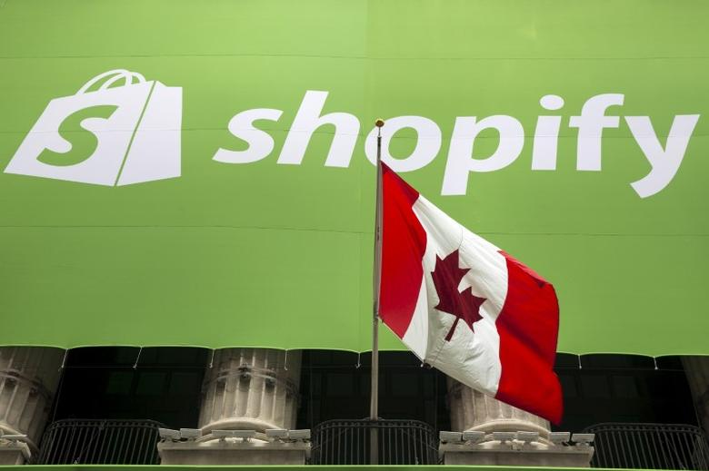 The logo of Shopify hangs behind the Canadian flag after the company's IPO at the New York Stock Exchange May 21, 2015. Picture taken May 21, 2015. REUTERS/Lucas Jackson