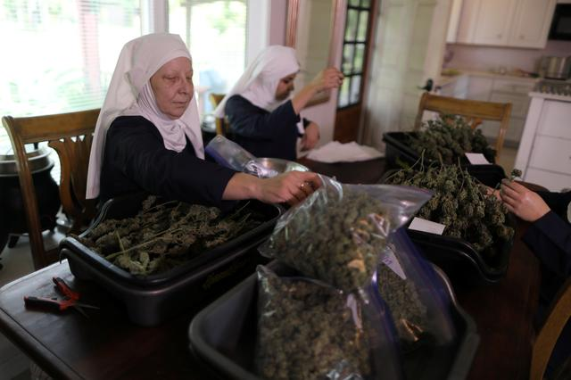 California ''weed nun'' Christine Meeusen, 57, who goes by the name Sister Kate (L), and India Delgado, who goes by the name Sister Eevee, trim hemp in the kitchen at Sisters of the Valley near Merced, California, U.S., April 18, 2017. REUTERS/Lucy Nicholson