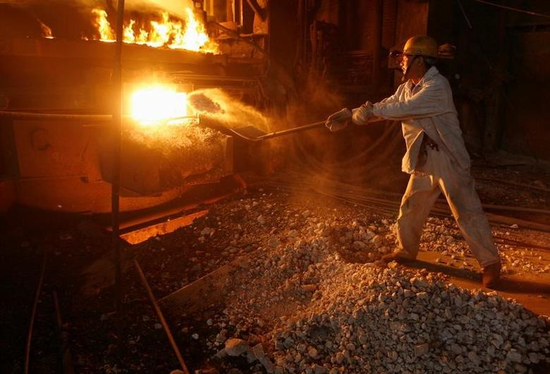 FILE PHOTO - A labourer shovels iron ore into a steel ladle at Wuhan Iron and Steel Group in the capital of central China's Hubei province October 17, 2007. REUTERS/Stringer/File Photo