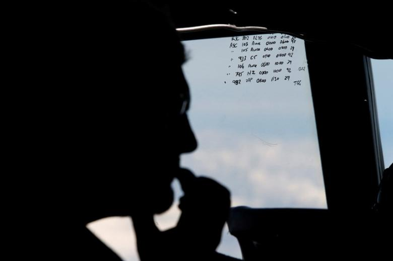 A crew member aboard a Royal New Zealand Air Force P-3K2 Orion aircraft is pictured alongside handwritten notes of other search craft in the area, during a search for the missing Malaysian Airlines flight MH370 over the southern Indian Ocean, March 29, 2014. REUTERS/Jason Reed/Files